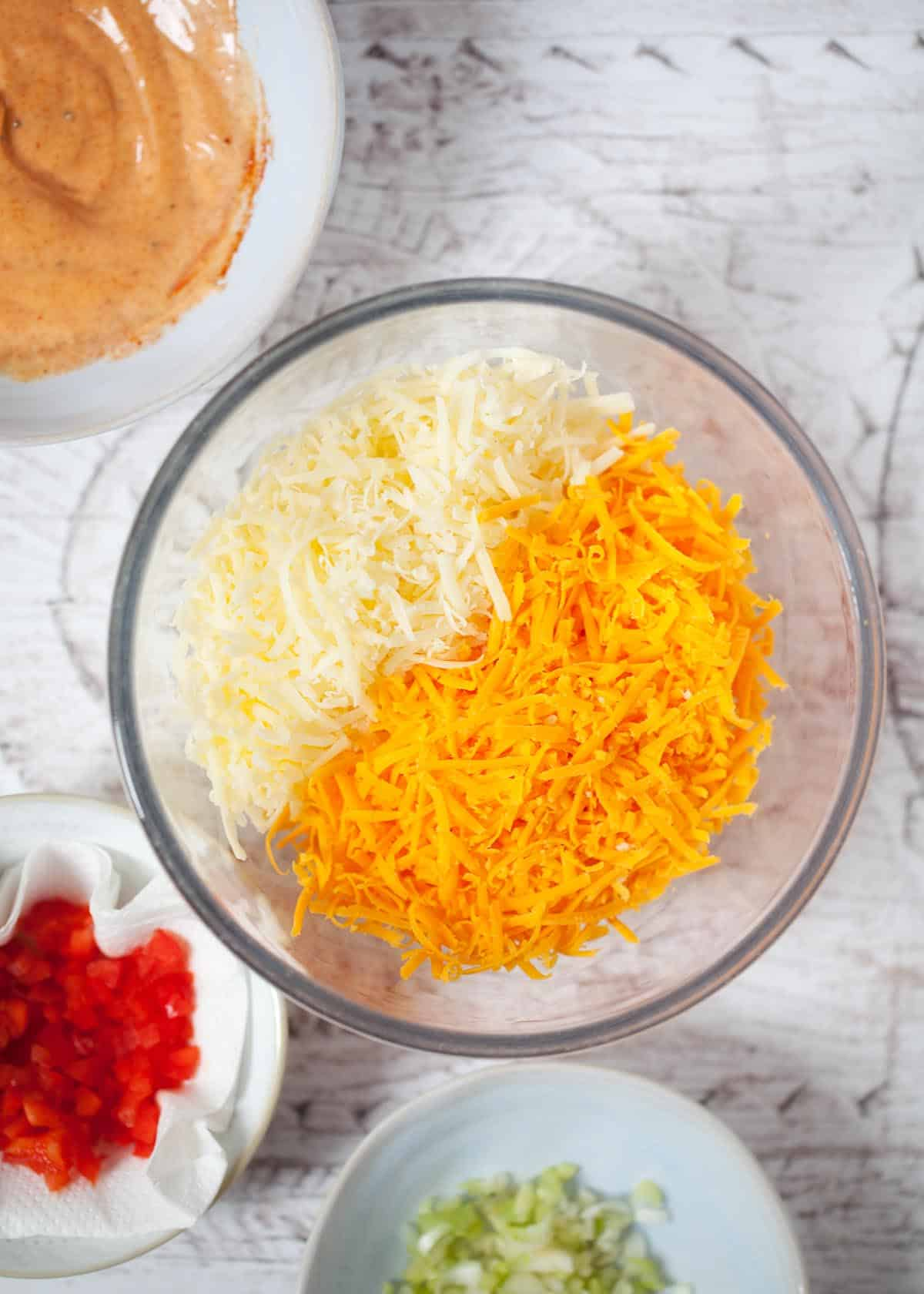 Two types of cheese (cheddar and red Leicester) finely grated into a bowl