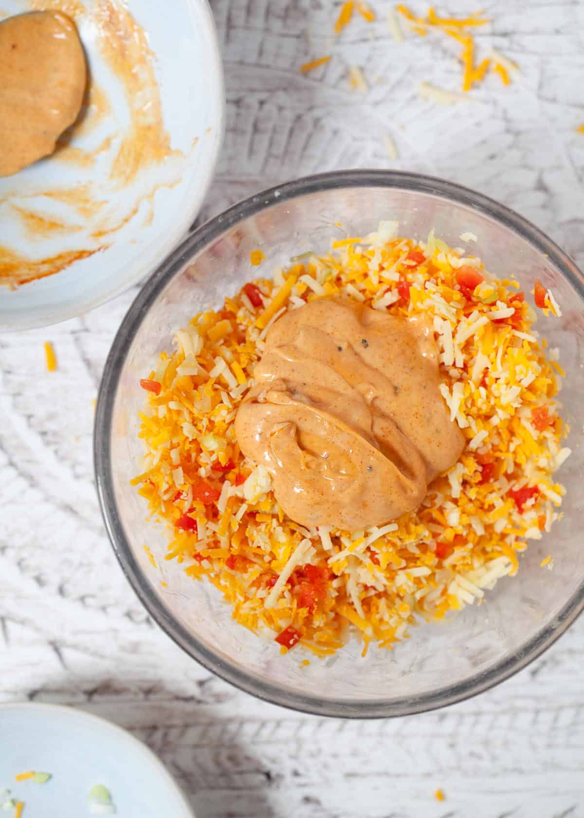 making cheese savoury sandwich filling by mixing grated cheese, red pepper, onion and paprika mayonnaise