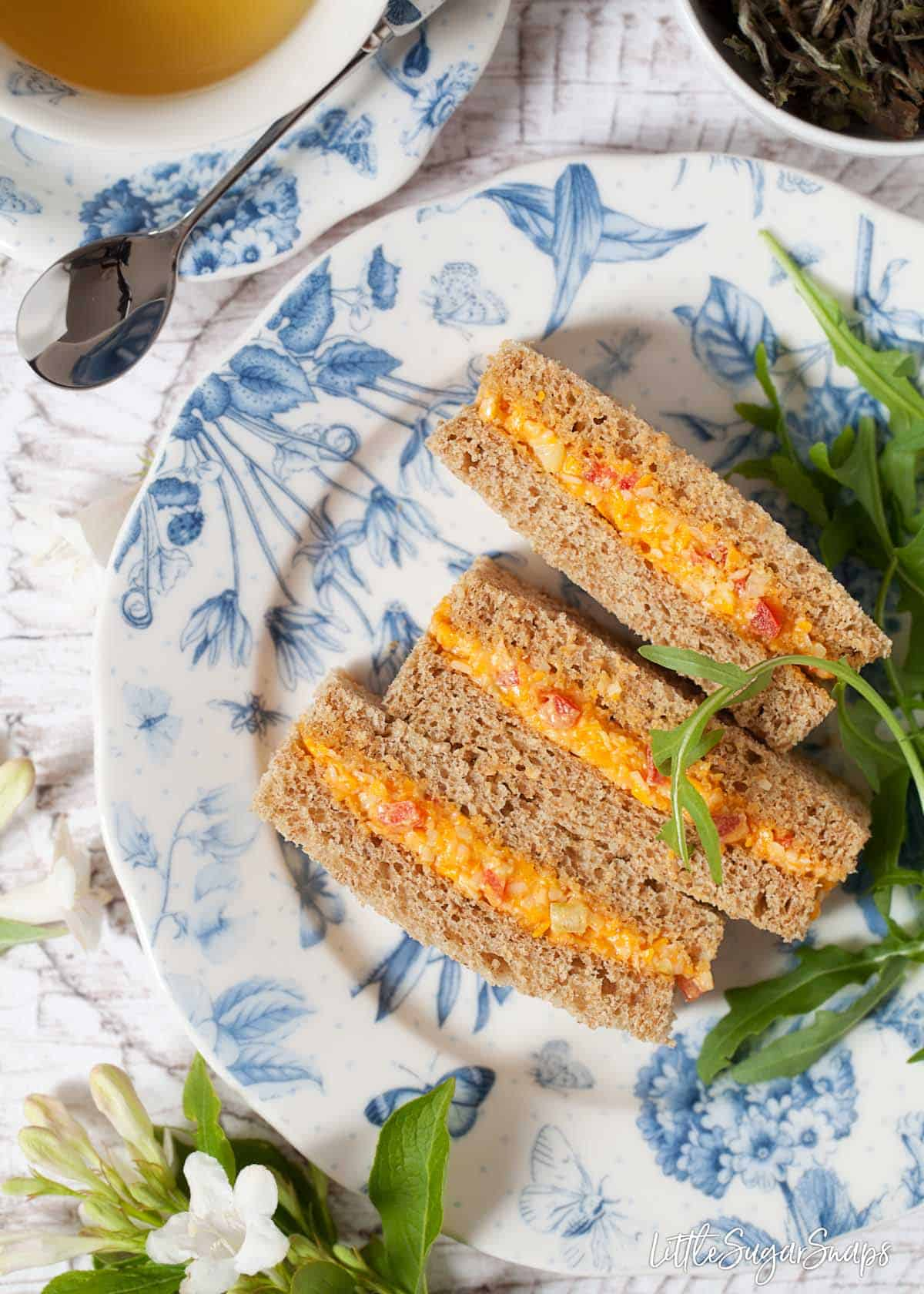 Three cheese savoury sandwiches are sitting on a pretty blue and white plate.