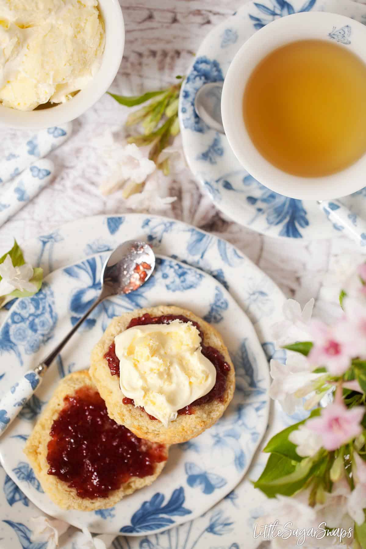 An overhead view of an English scone topped with jam and clotted cream, served with a cup of tea as part of classic afternoon tea