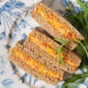 Cheese Savoury Sandwich for Afternoon Tea cut dainty and served on pretty crockery with a rocket leaf garnish