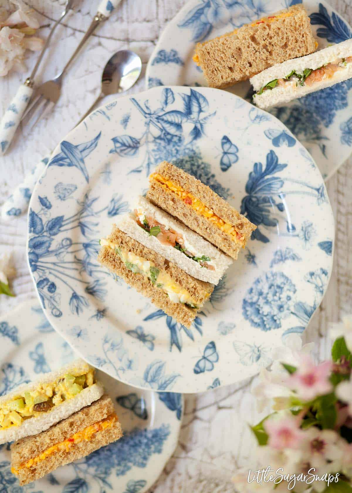 Mixed afternoon tea sandwiches served on blue and white crockery. The middle plate has 3 sandwiches and 2 smaller plates at each side have 2 sandwiches. Flavours include cheese savoury sandwiches, smoked salmon and cream cheese sandwiches, devilled egg sandwiches and coronation chicken sandwiches