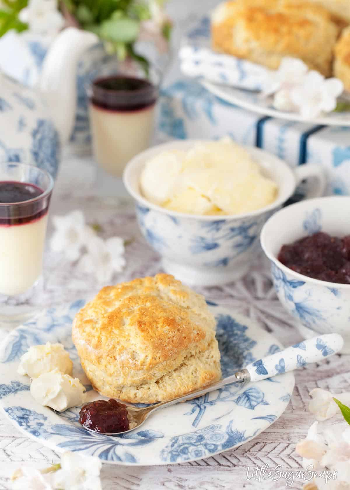 An English scone on a pretty blue and whote side plate with 2 scoops of clotted cream and a spoon with raspberry jam resting on the plate. Cupfuls of cream and jam are in the background along with more scones, glasses of creamy lemon posset dessert and flowers