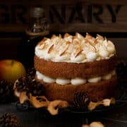 A 2 layer cinnamon and apple cake sandwiched together with buttercream and decorated with dried apple and ground cinnamon. Presented on a wire rack with slices of apple and pine cones around it