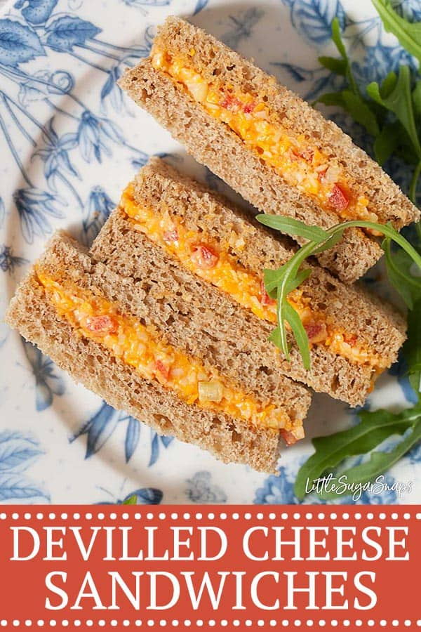 Dainty afternoon tea sandwiches filled with devilled cheese with a side garnish of rocket