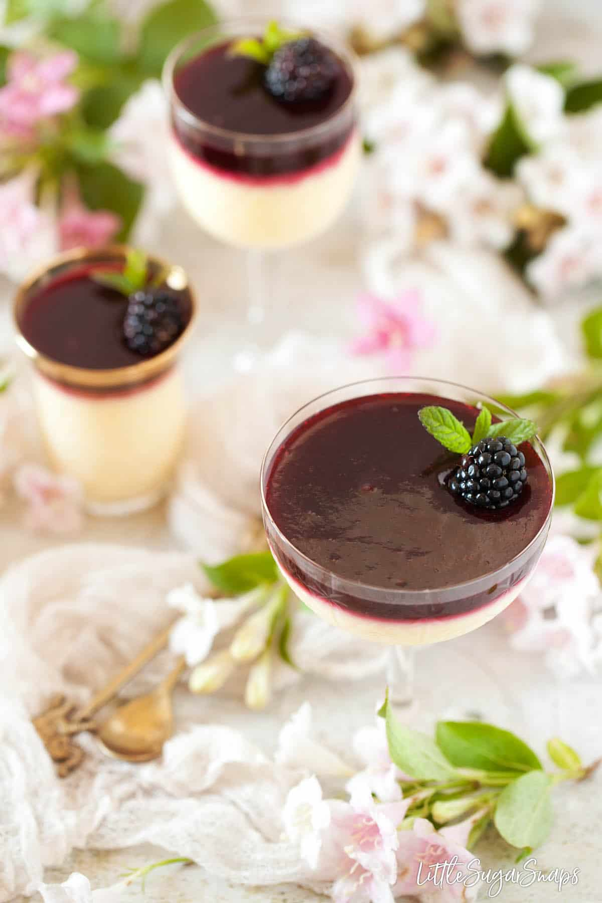 Glasses of lemon posset with blackberry sauce