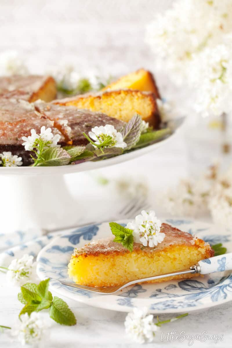 A slice of orange semolina cake topped with flowers and mint on a plate.
