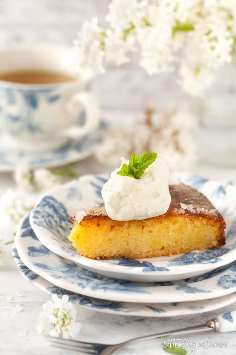 A slice of flourless orange semolina cake topped with chantilly cream.