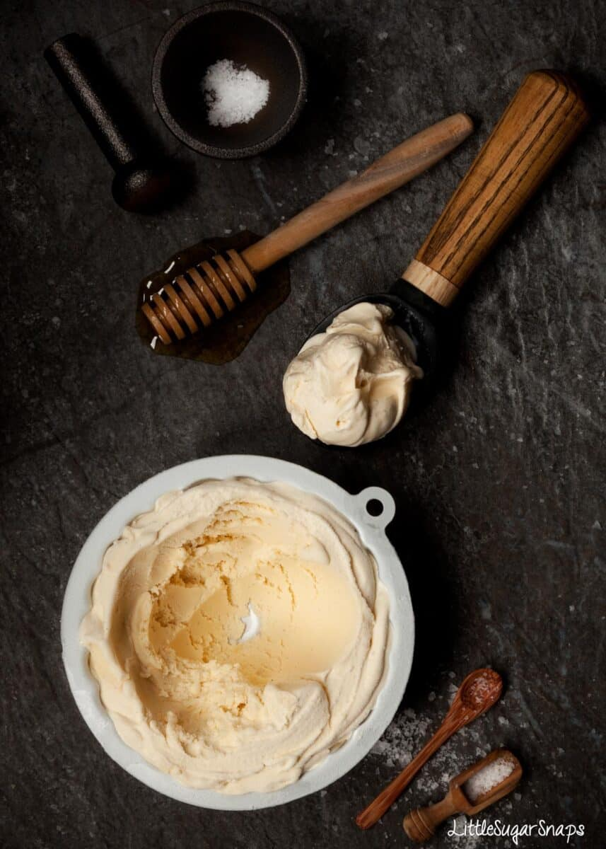 Salted honey ice cream part scooped out of a tin with ingredients in shot