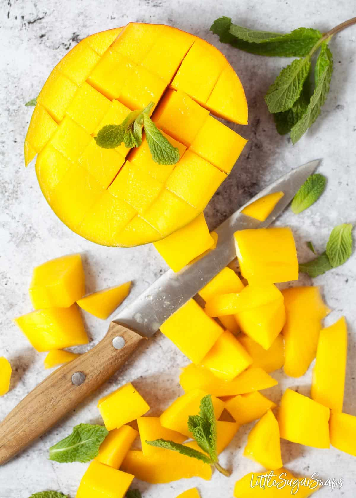 Chunks of mango and half a mango with cuts in it, on a worktop with a sharp kinfe and fresh mint leaves
