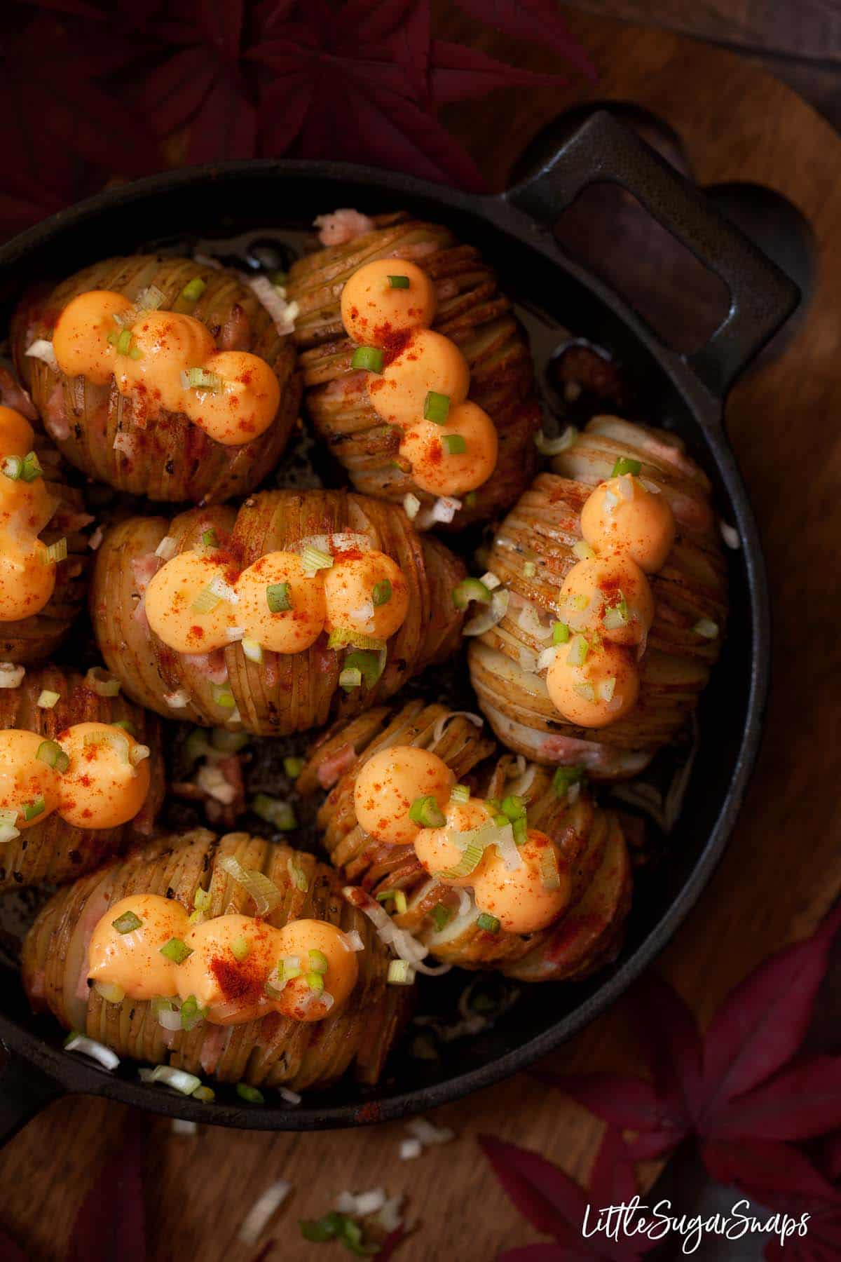 Cheesy Hasselback potatoes filled with bacon and topped with cheese spread and onion
