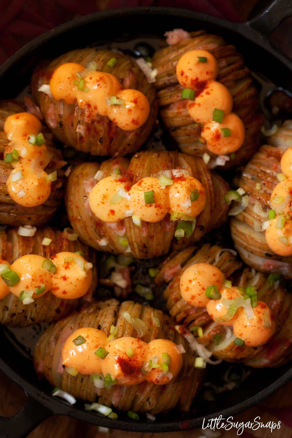 Close up of cheesy hasselback potatoes filled with bacon and topped with cheese spread
