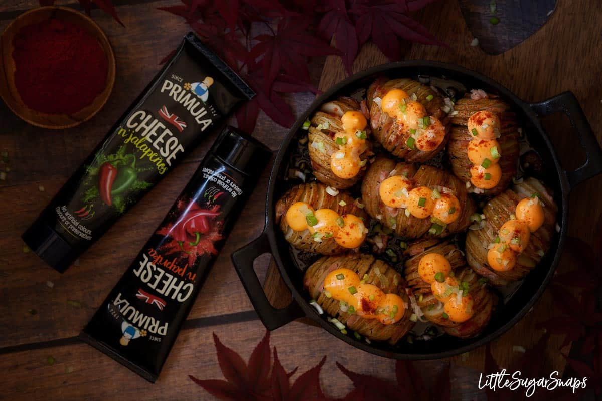 Cast iron skillet holding Hasselback potatoes filled with bacon and topped with cheese spread, chopped scallion onion and dusted with paprika. Also in shot are tubes of cheese spread, red leaves and a wooden bowl with paprika in it