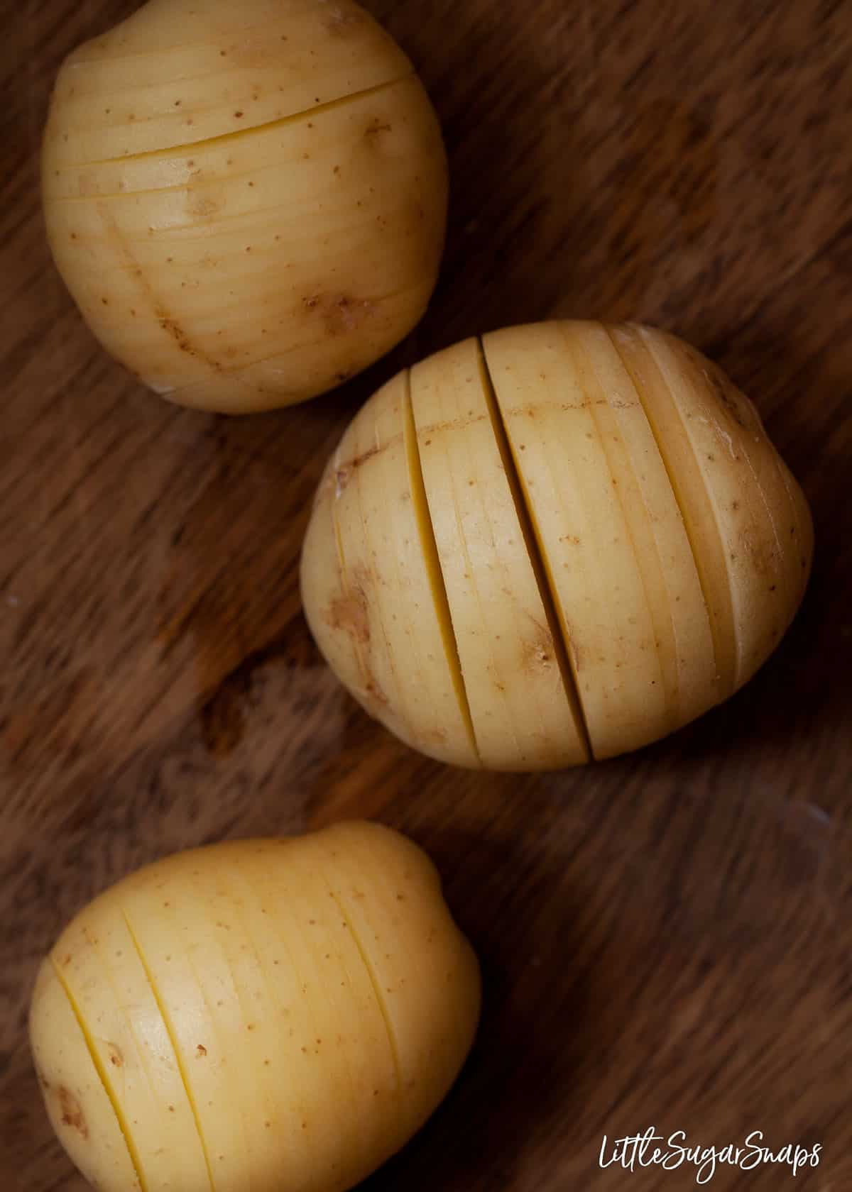 Process shot - new potatoes with vertical slits cut into them