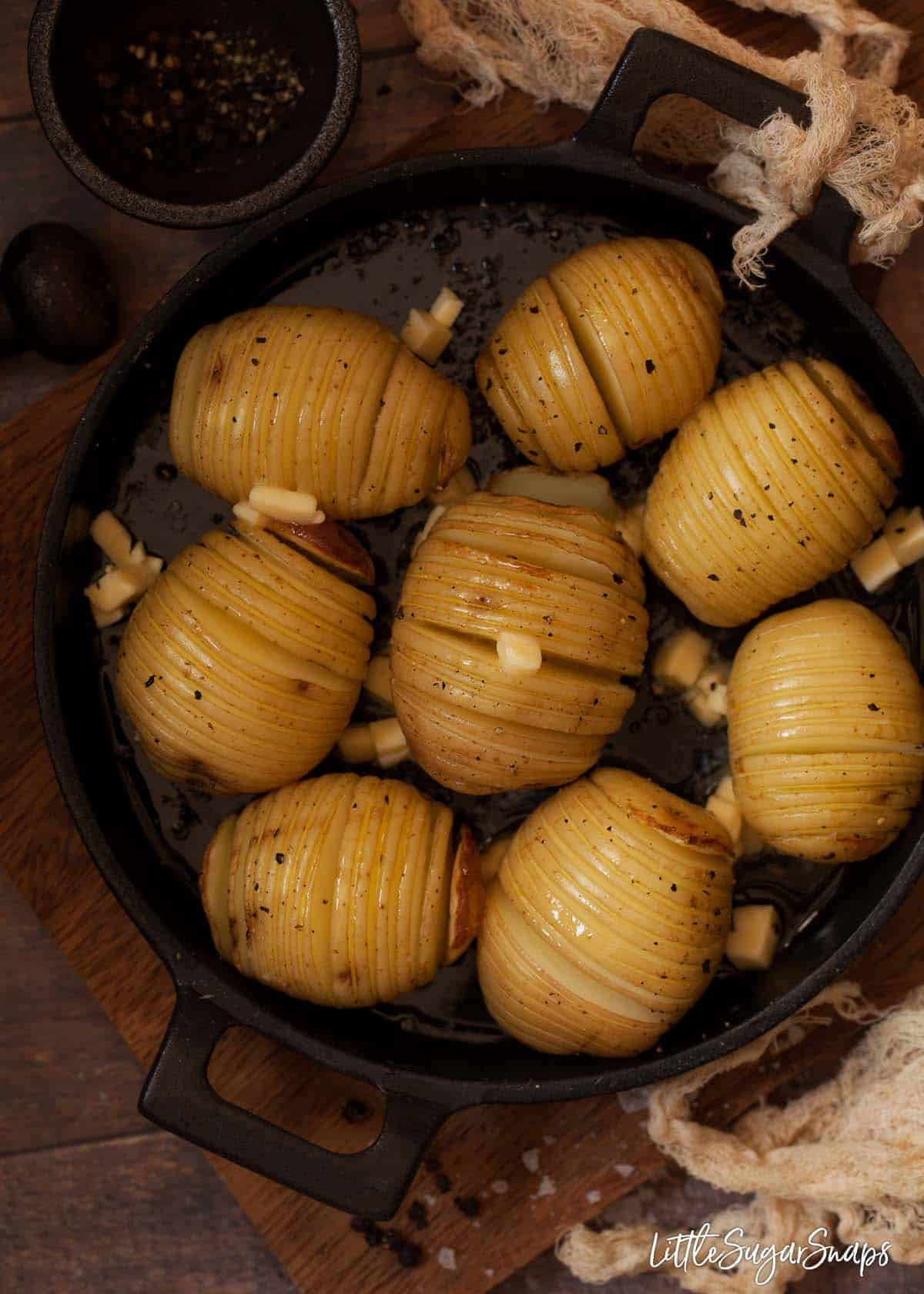 Process shot - adding butter to part-cooked Hasselback potatoes in a cooking pan