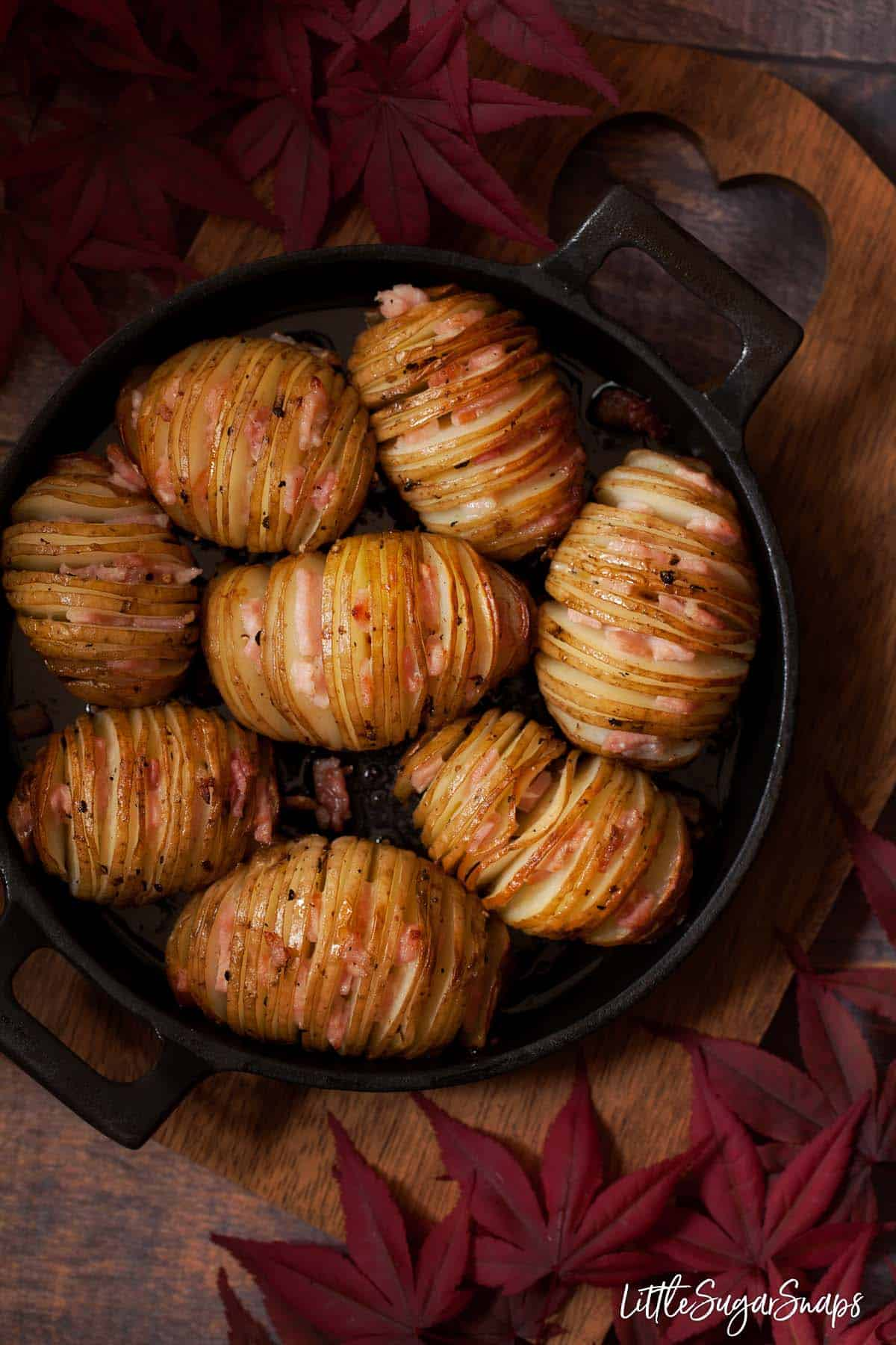 Cast iron skillet holding freshly baked hasselback potatoes stuffed with bacon.