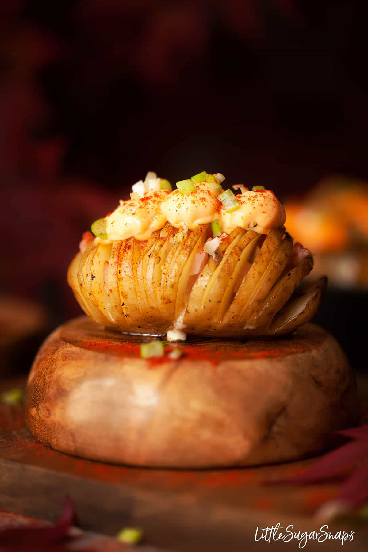 A cheesy hasselback potato filled with bacon sitting on an upturned wooden bowl.