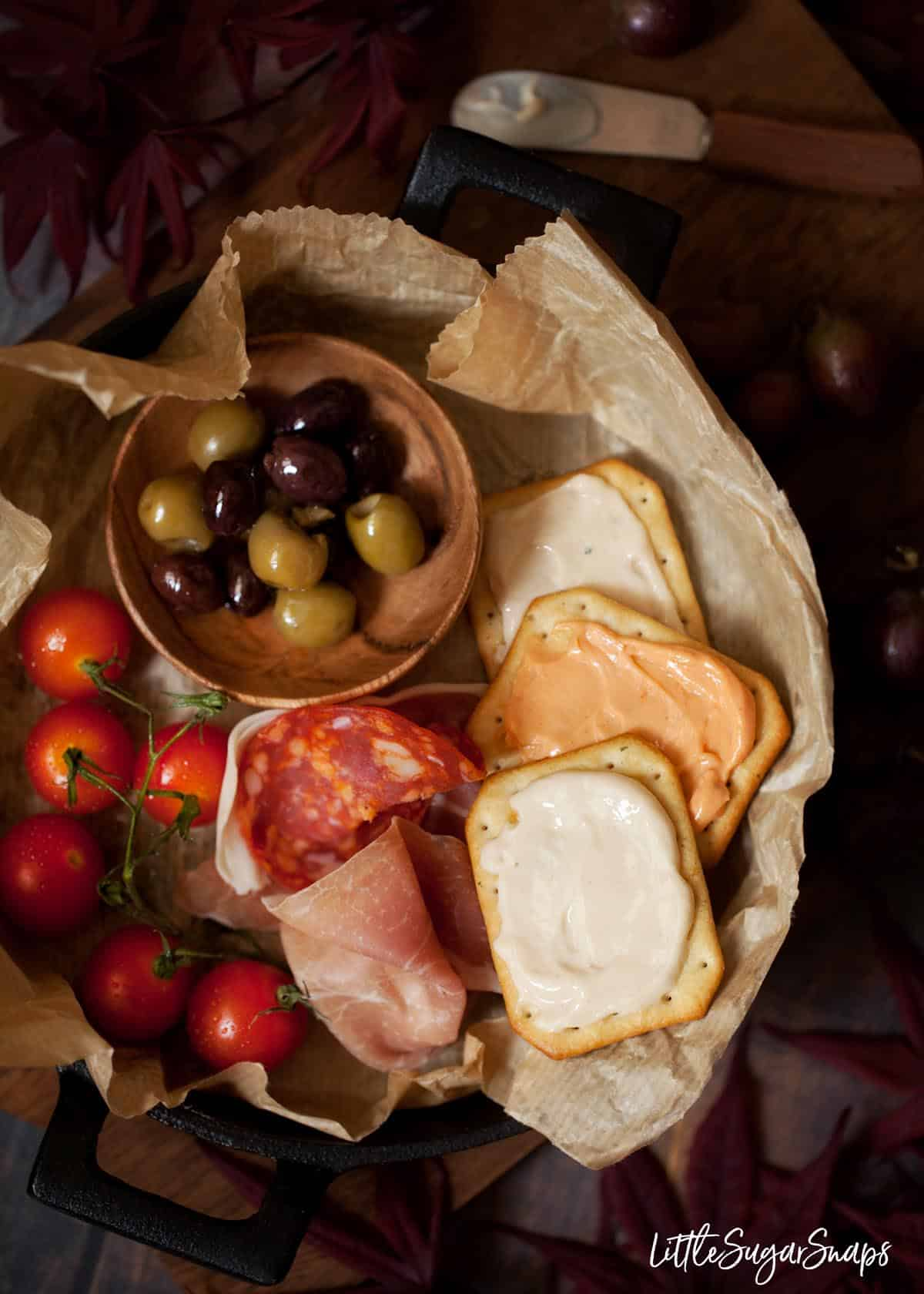 A tray of crackers topped with cheese spread served with olives, cured meats and cherry tomatoes on the vine.