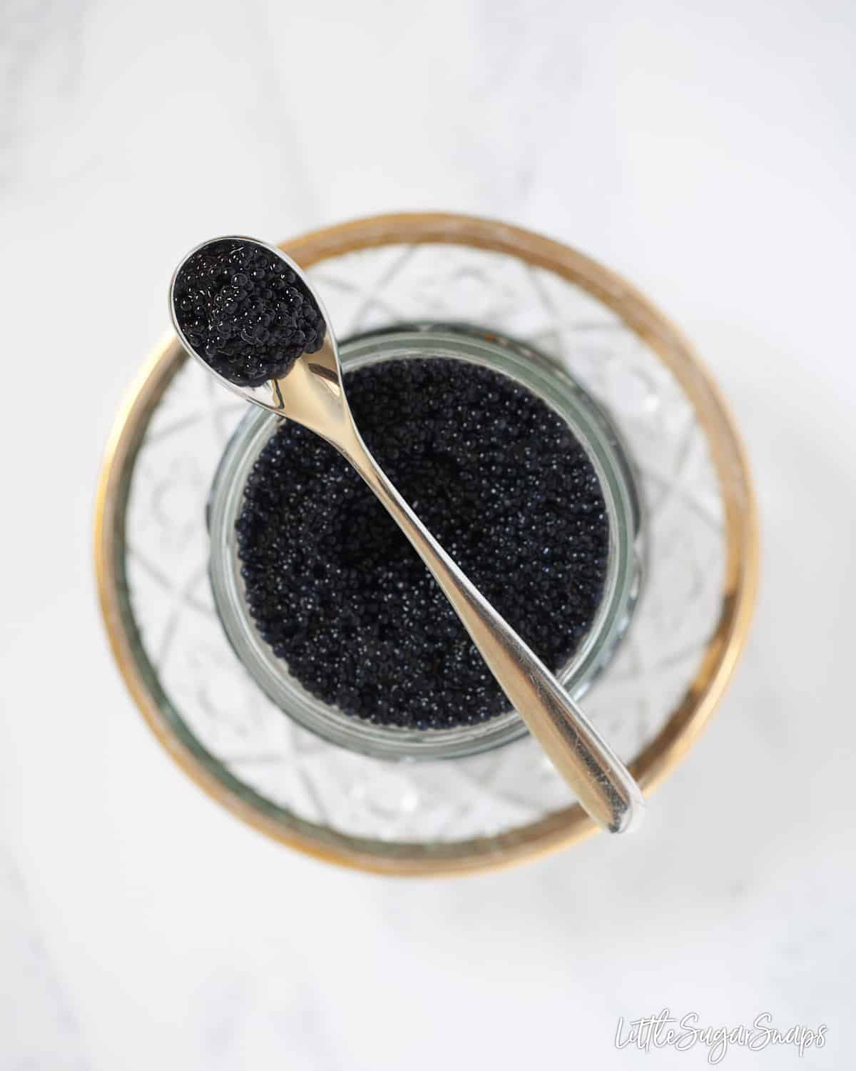 A glass jar of caviar on a pretty plate. There is a small spoon resting across the jar with some caviar on it