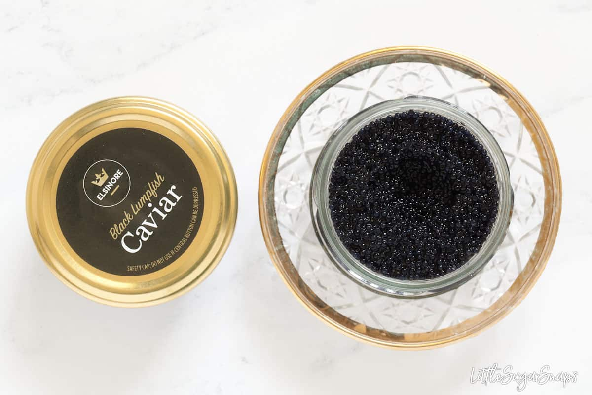 Two pots of black lumpfish caviar side by side. One is open, the other has its lid on
