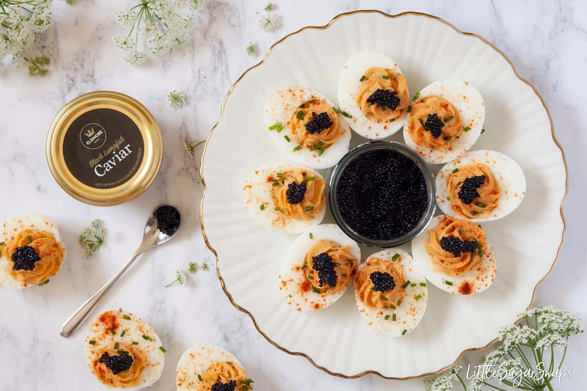 A plate of devilled eggs with caviar and several jars of caviar on a marble worktop