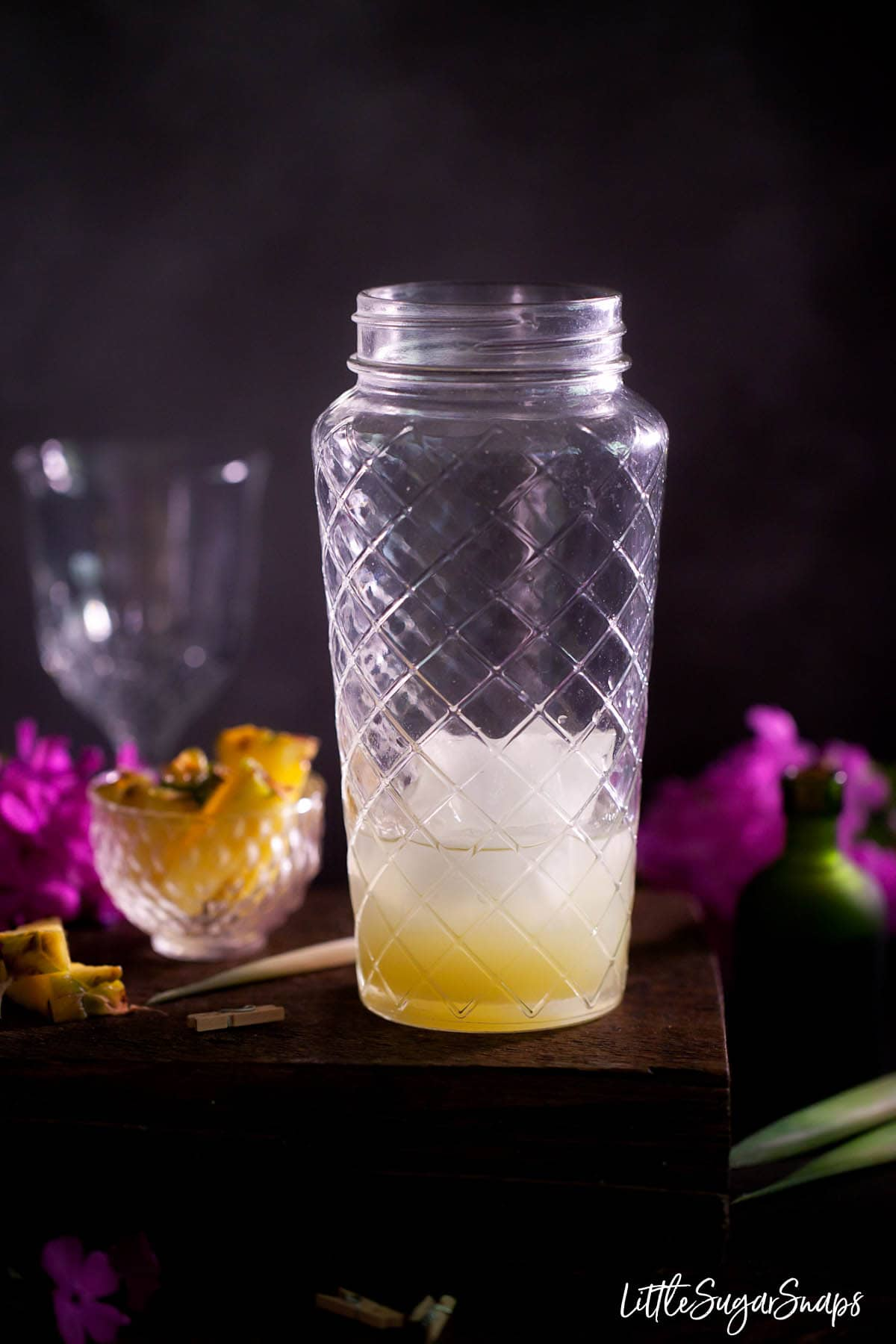 Ingredients for a Royal Hawaiian in a cocktail shaker: ice, gin and pineapple juice