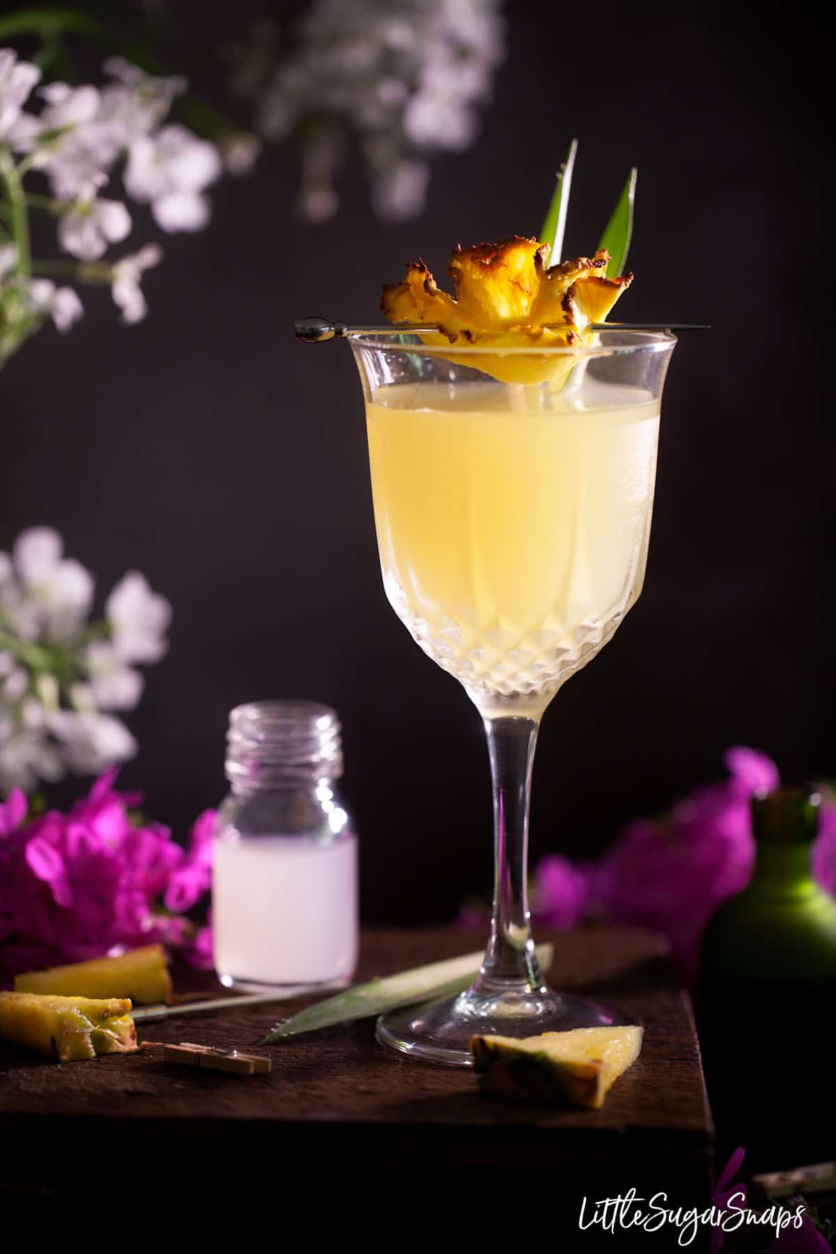 A Royal Hawaiian Cocktail garnished with dried pineapple and fresh pineapple leaves