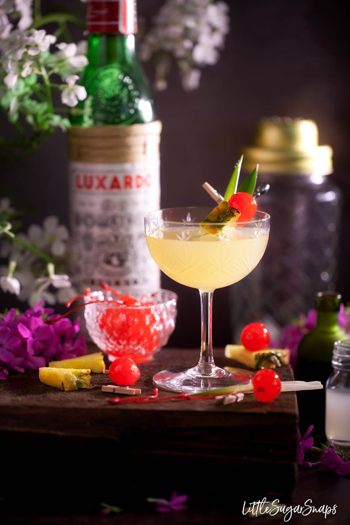 A gin, pineapple and cherry cocktail garnished with fresh pineapple and maraschino cherry.