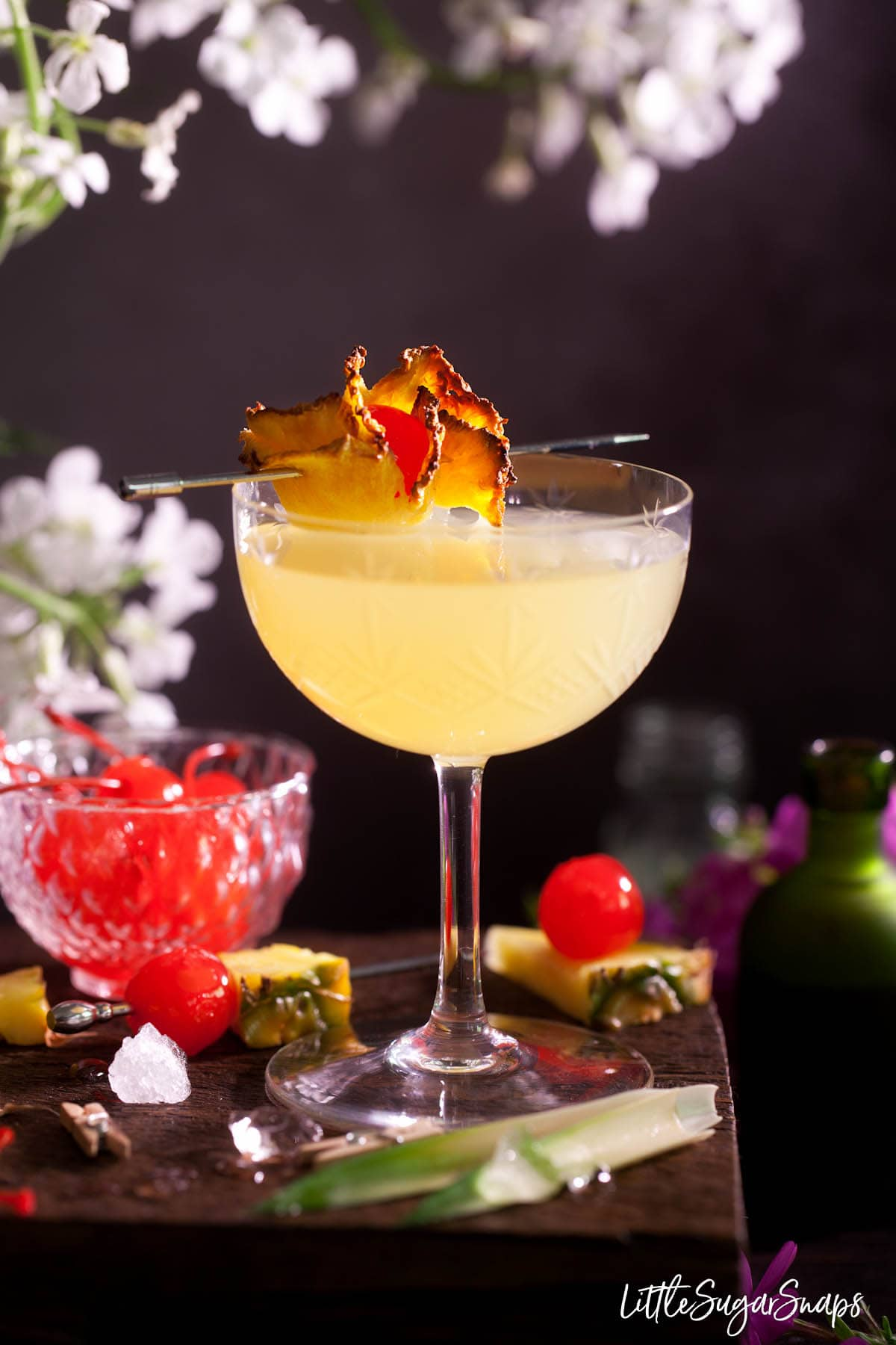 A gin and pineapple cocktail garnished with dried pineapple and maraschino cherry.
