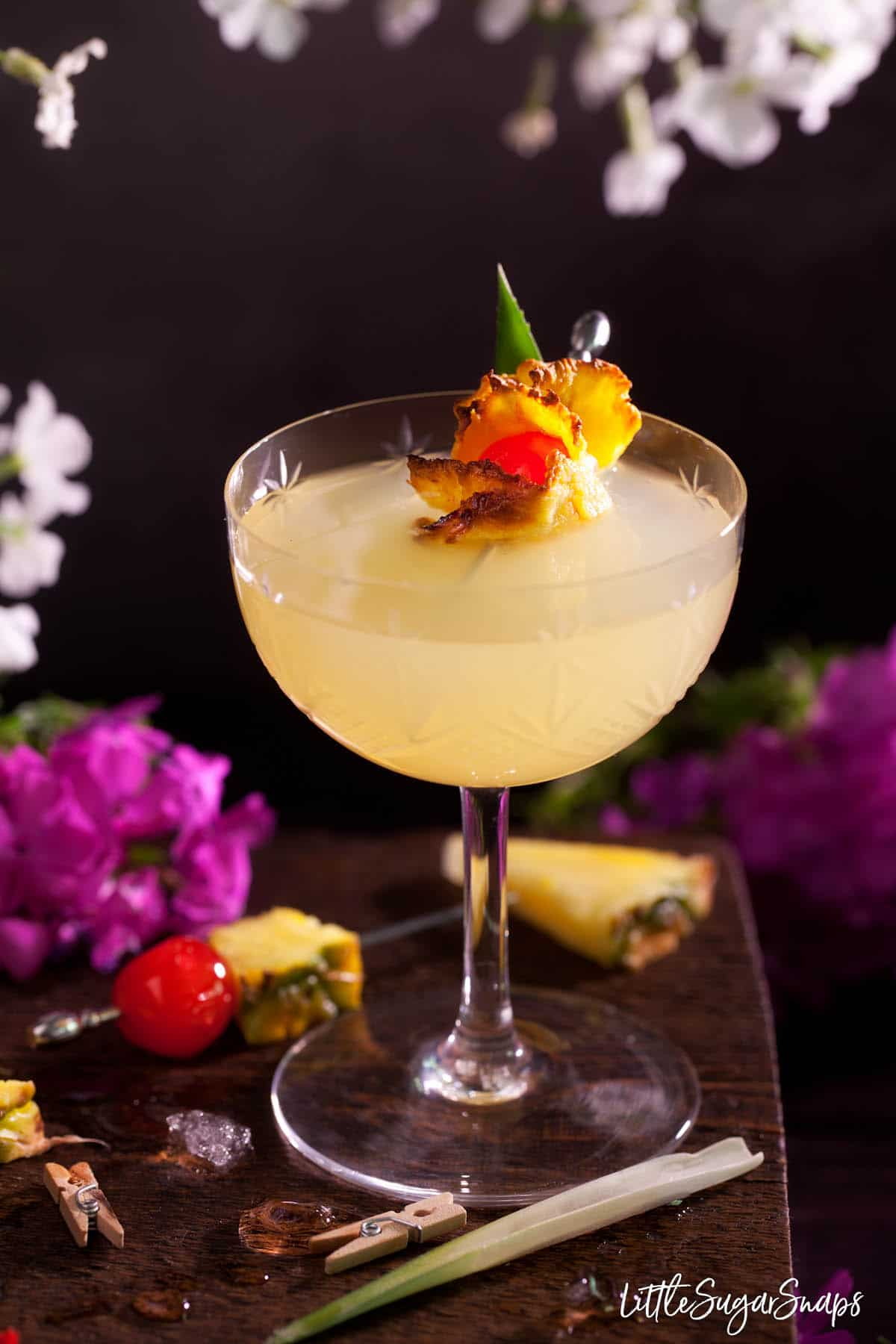 A Royal Hawaiian cocktail garnished with oven-dried pineapple and a maraschino cherry