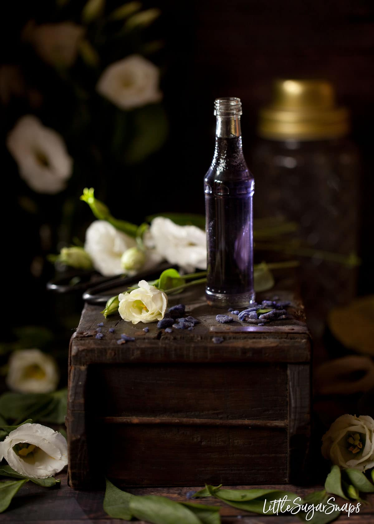A small bottle of violet flavoured syrup on a wooden block with candied violet pieces and white flowers on the box too. Rustic setting