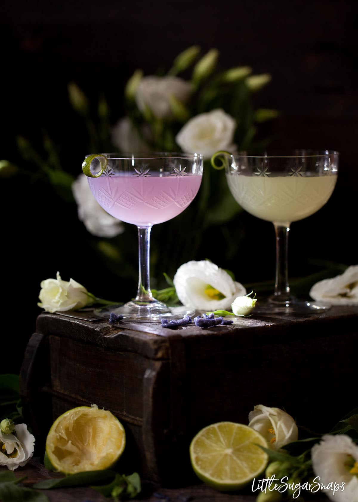 Two daiquiri cocktails on a wooden box. One is a classic lime daiquiri the other is light purple as it has been flavoured with violet. Candied violet pieces, lime halves and white flowers are in shot too