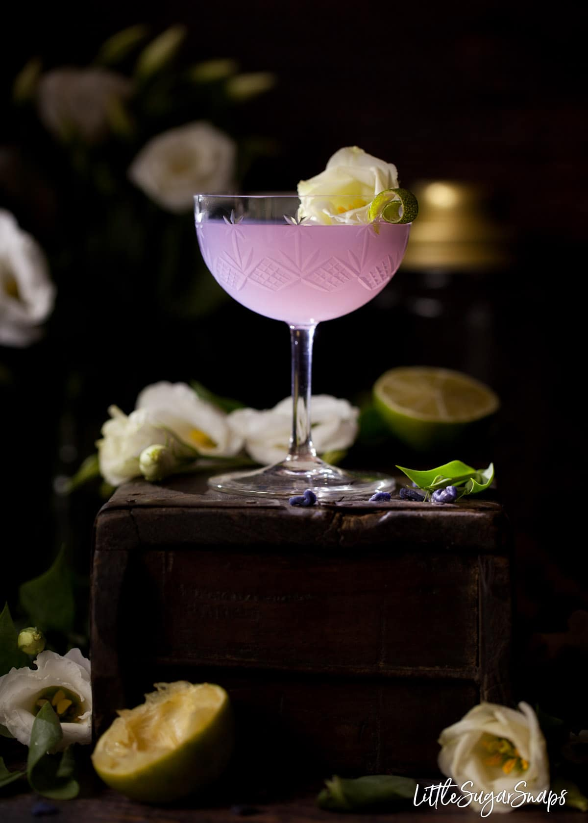 A violet cocktail on a wooden box. The drink is garnished with a curl of lime and a white flower