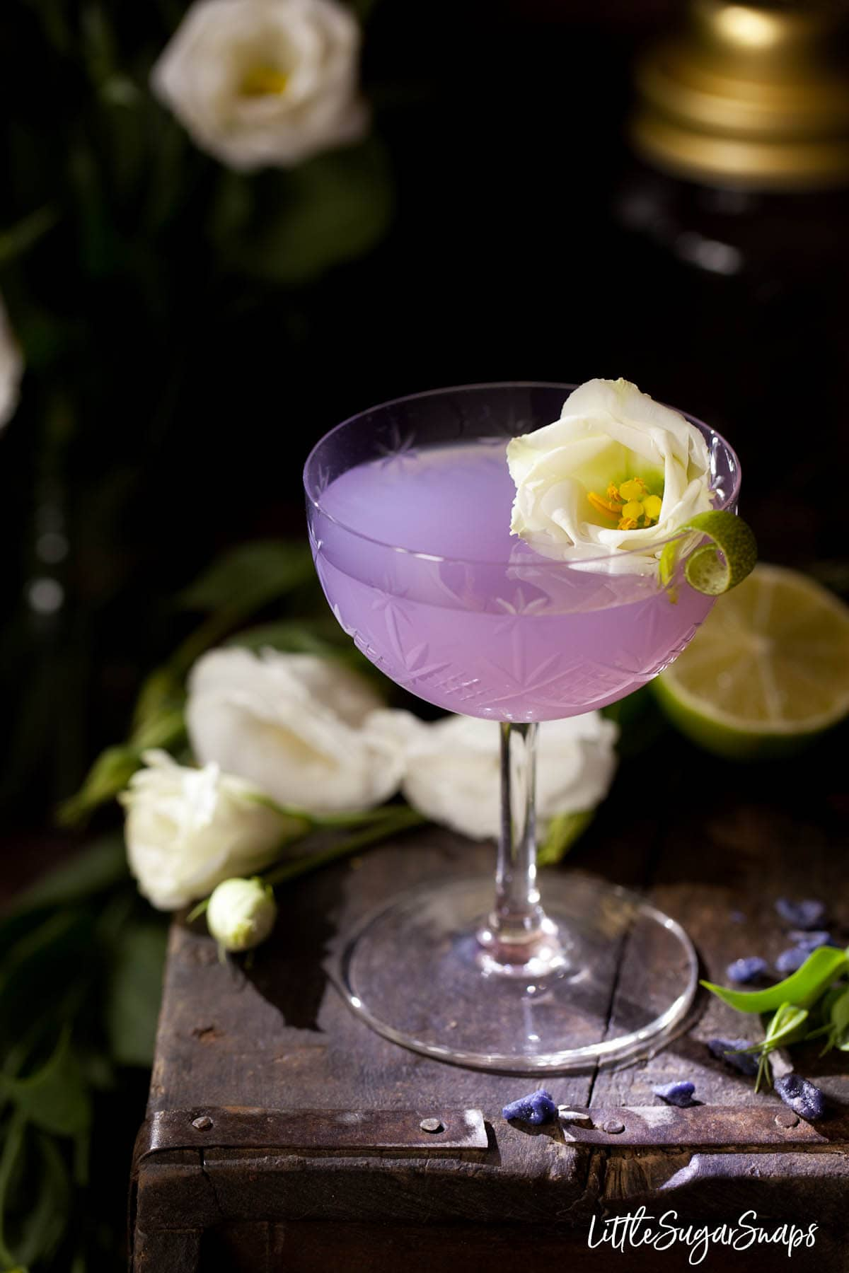 A purple coloured violet daiquiri cocktail with floral garnish
