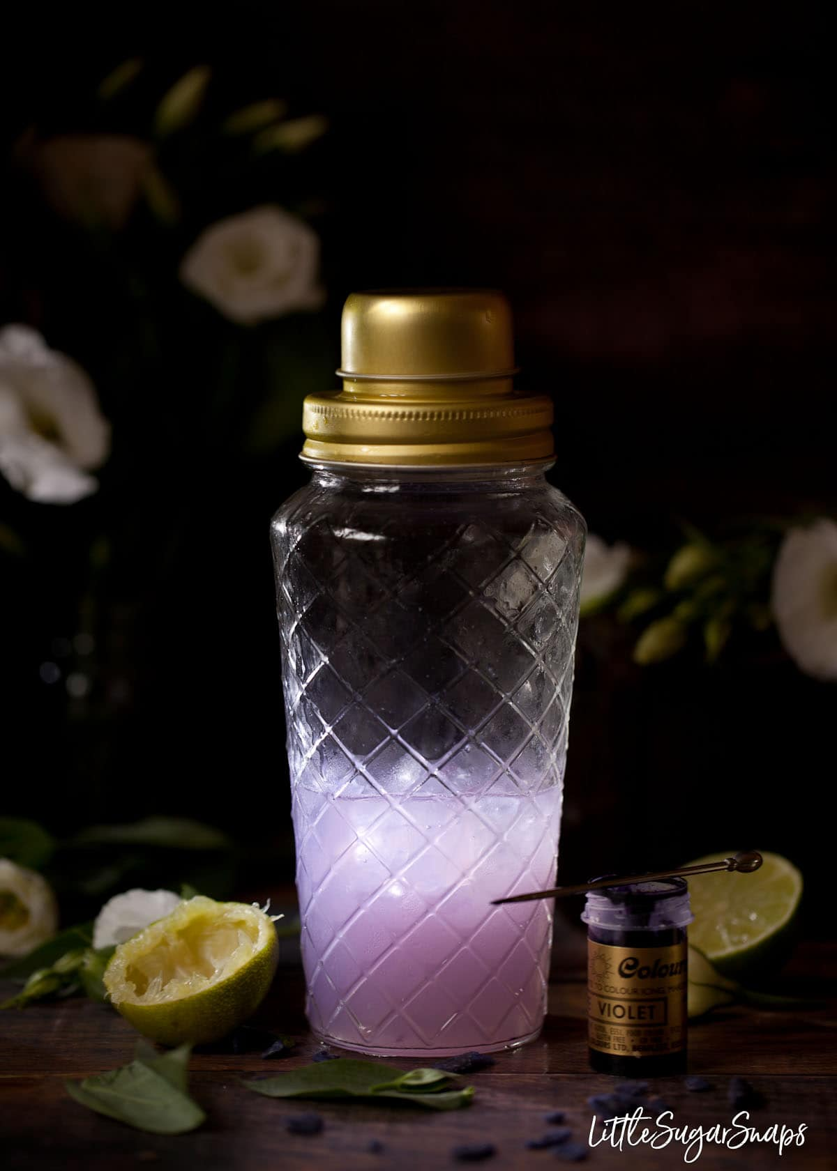 A purple violet cocktail in a shaker with lime halves and violet food dye in shot