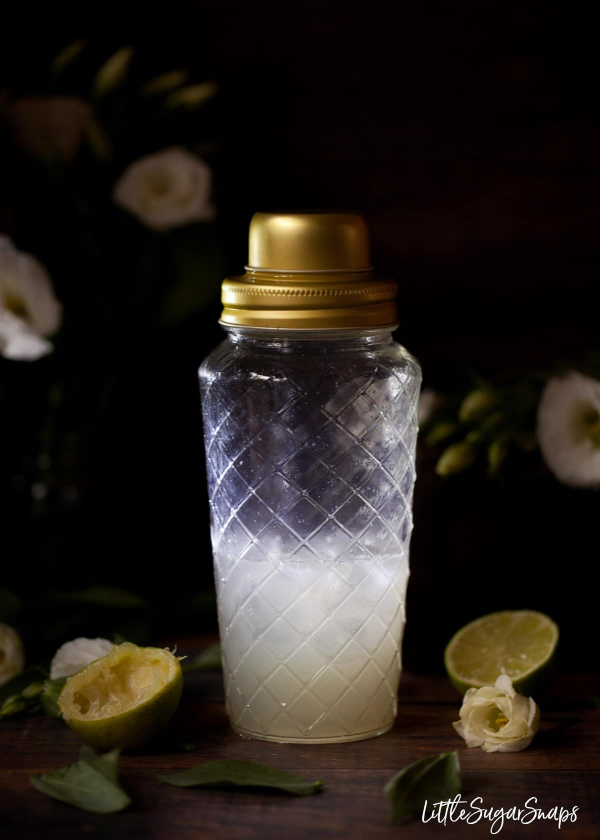 ingredients in a glass shaker with lime halves next to it and white flowers in the background
