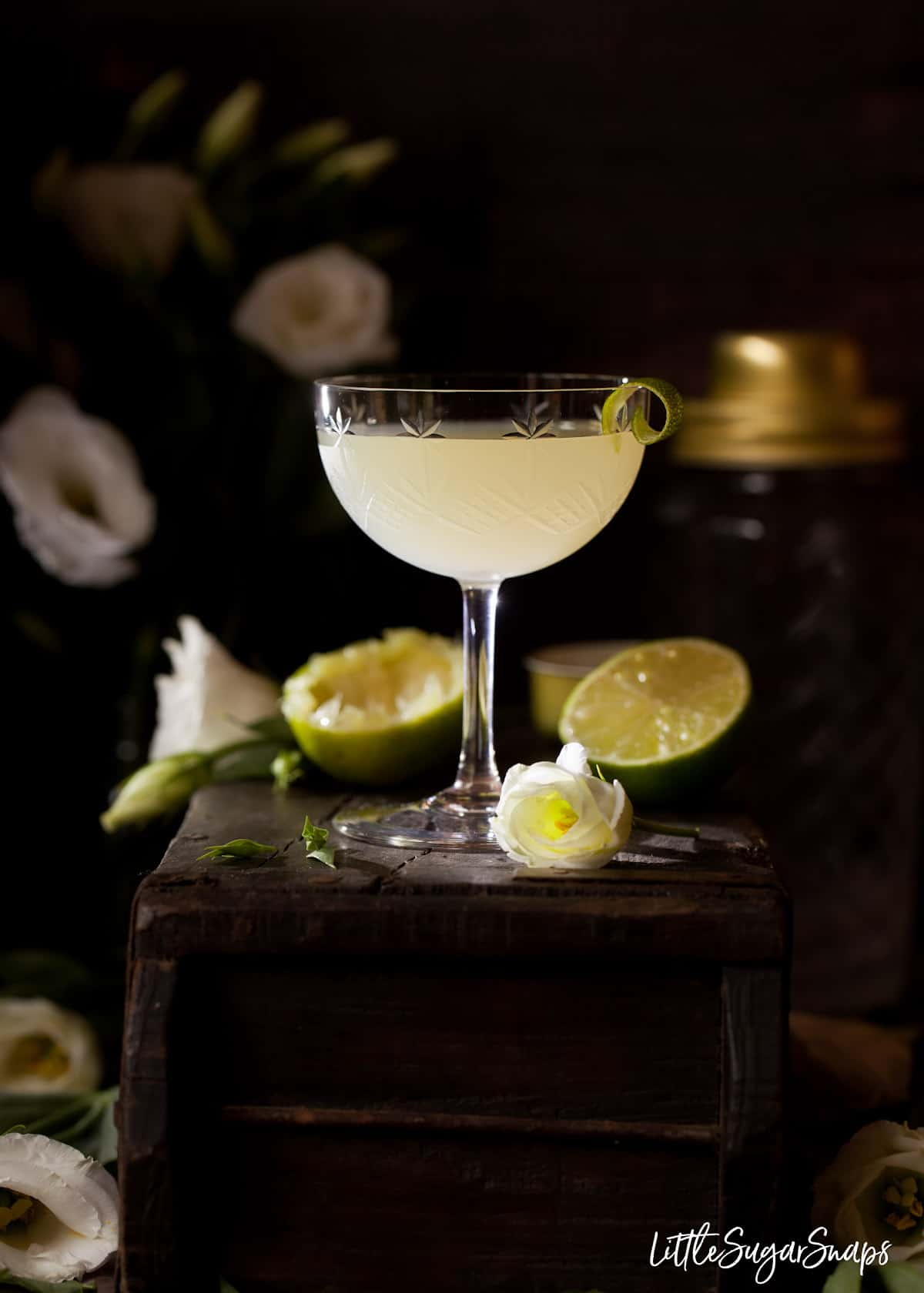 A classic daiquiri cocktail garnished with a curl of lime. It is served in a vintage cocktail glass and rests on a wooden block with white flowers and lime halves in the background