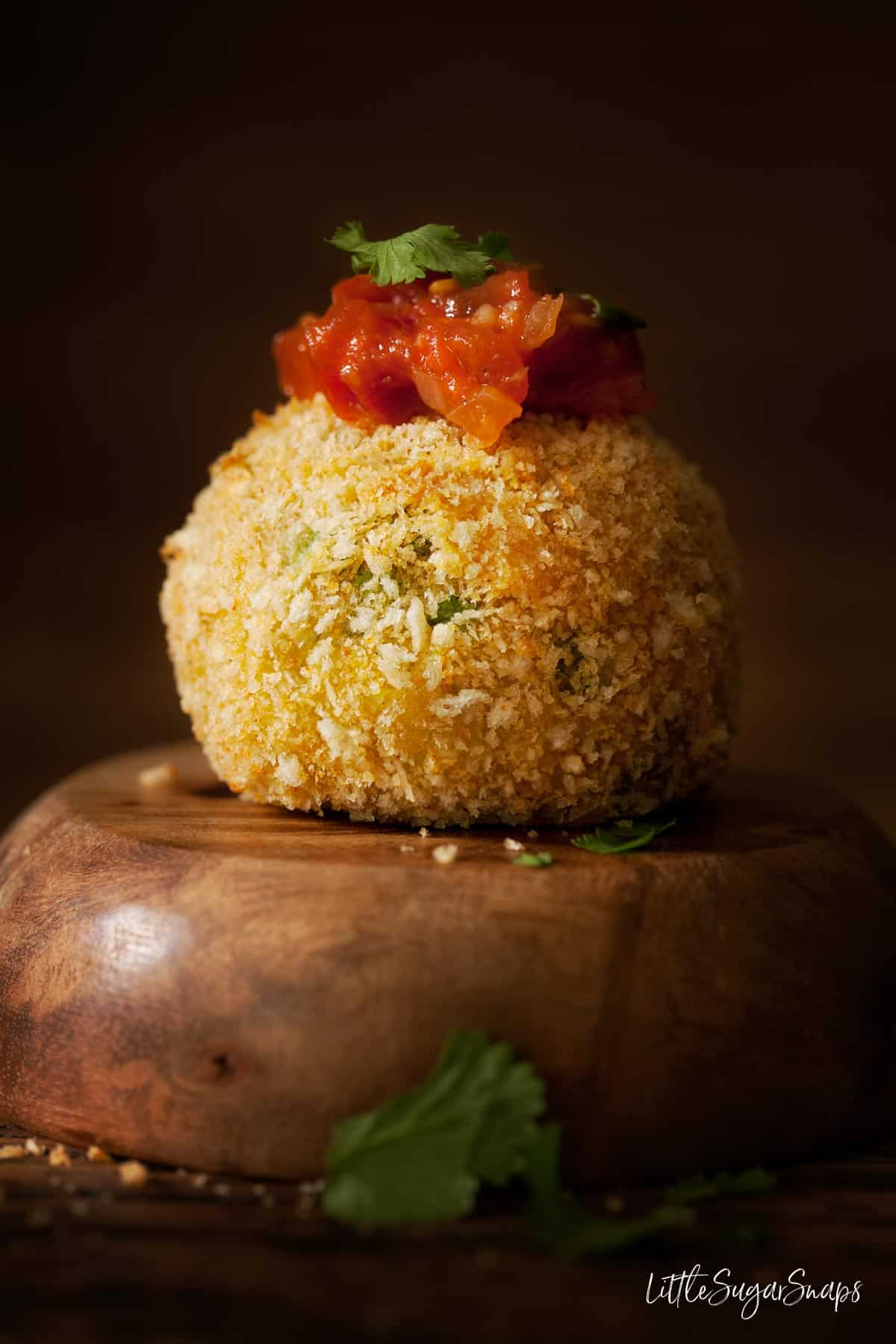 A smoked haddock fish cake with a spoonful of spiced tomato sauce