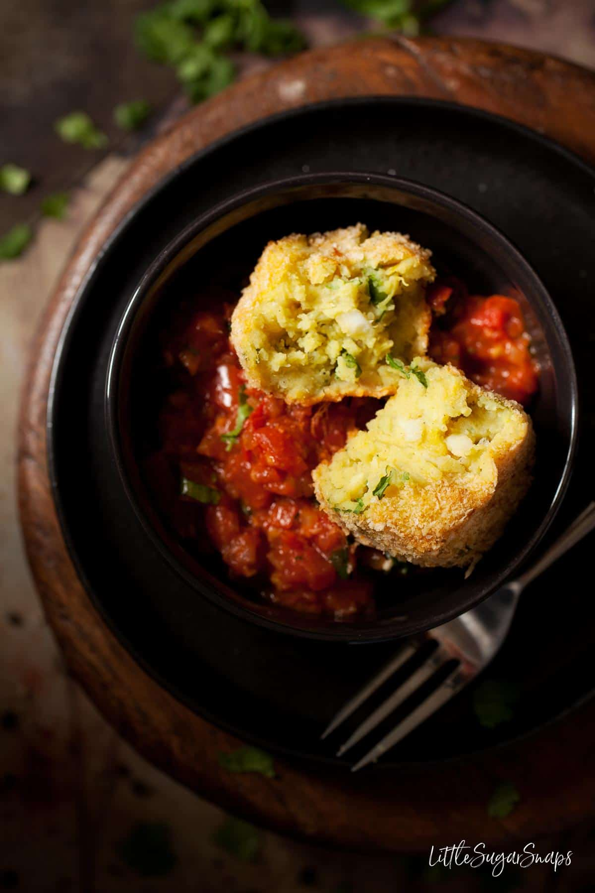 A cut open smoked haddock fish cake with spiced tomato sauce.
