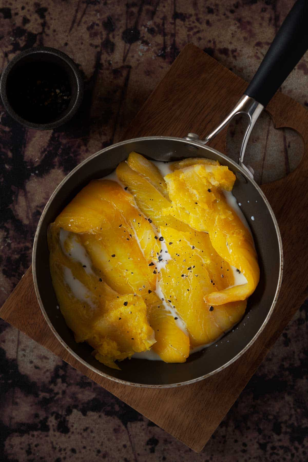 A cooking pan holding yellow dyed smoked haddock, milk and black pepper