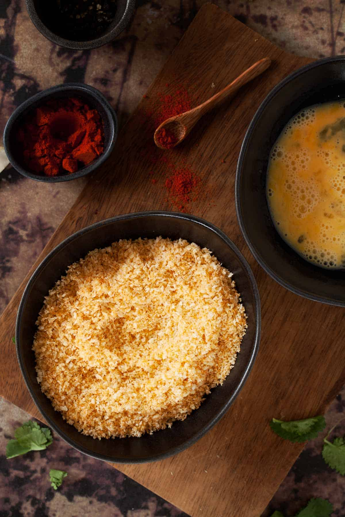 Panko breadcrumbs in a dark bowl with another bowl containing beaten egg next to it