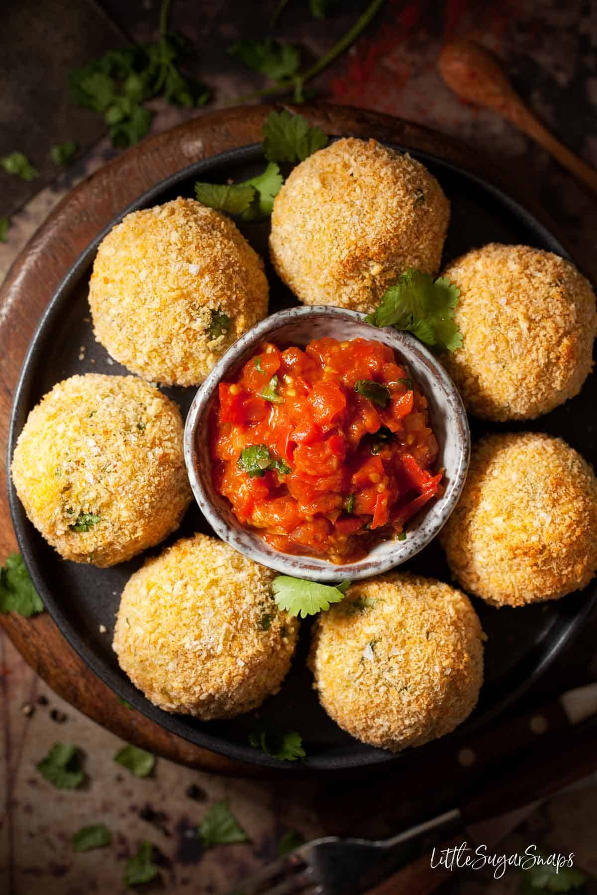Fish cake balls on a plate with a bowl of spiced tomato sauce