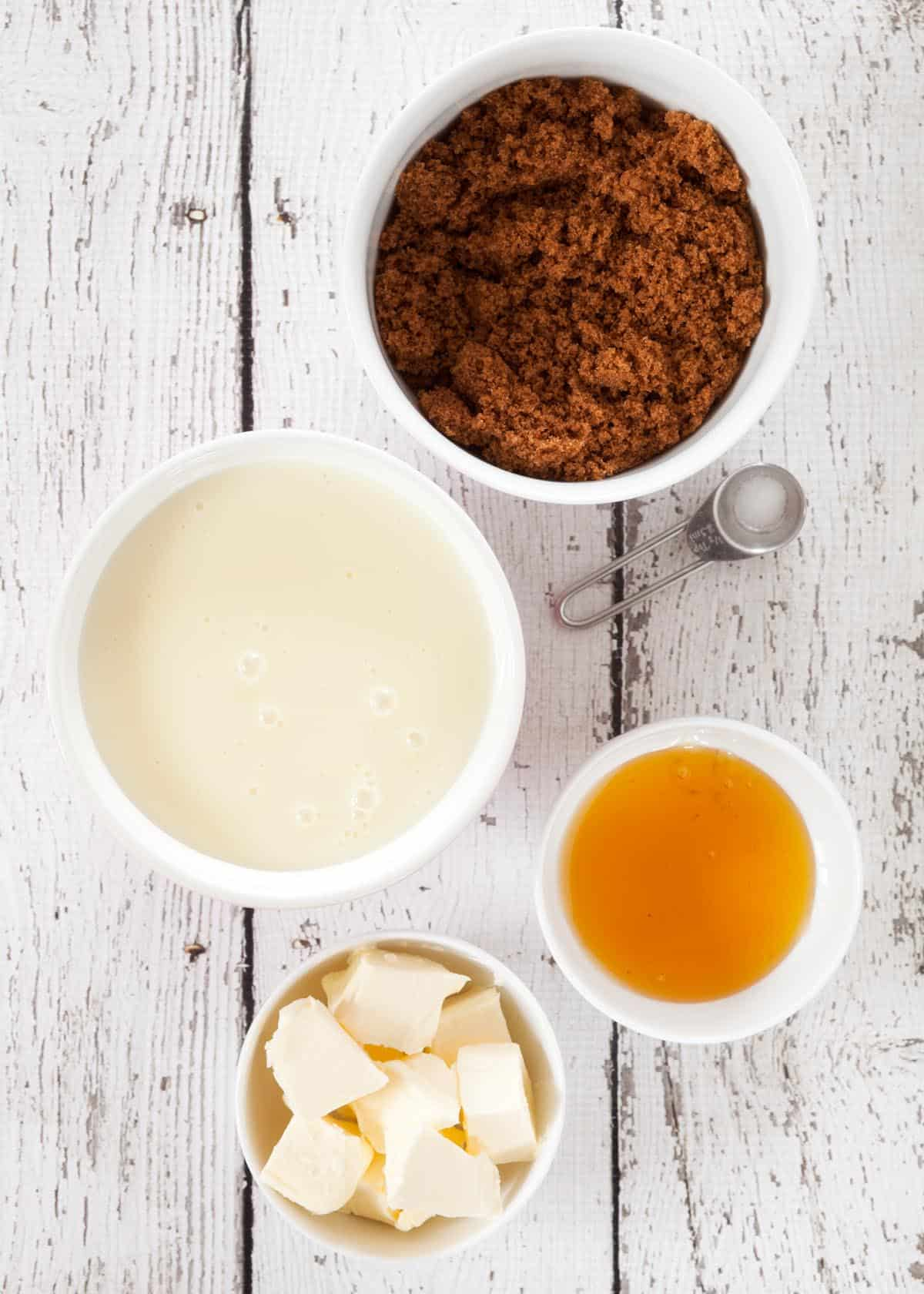 Ingredients for caramel in bowls: condensed milk, golden syrup, butter and brown sugar