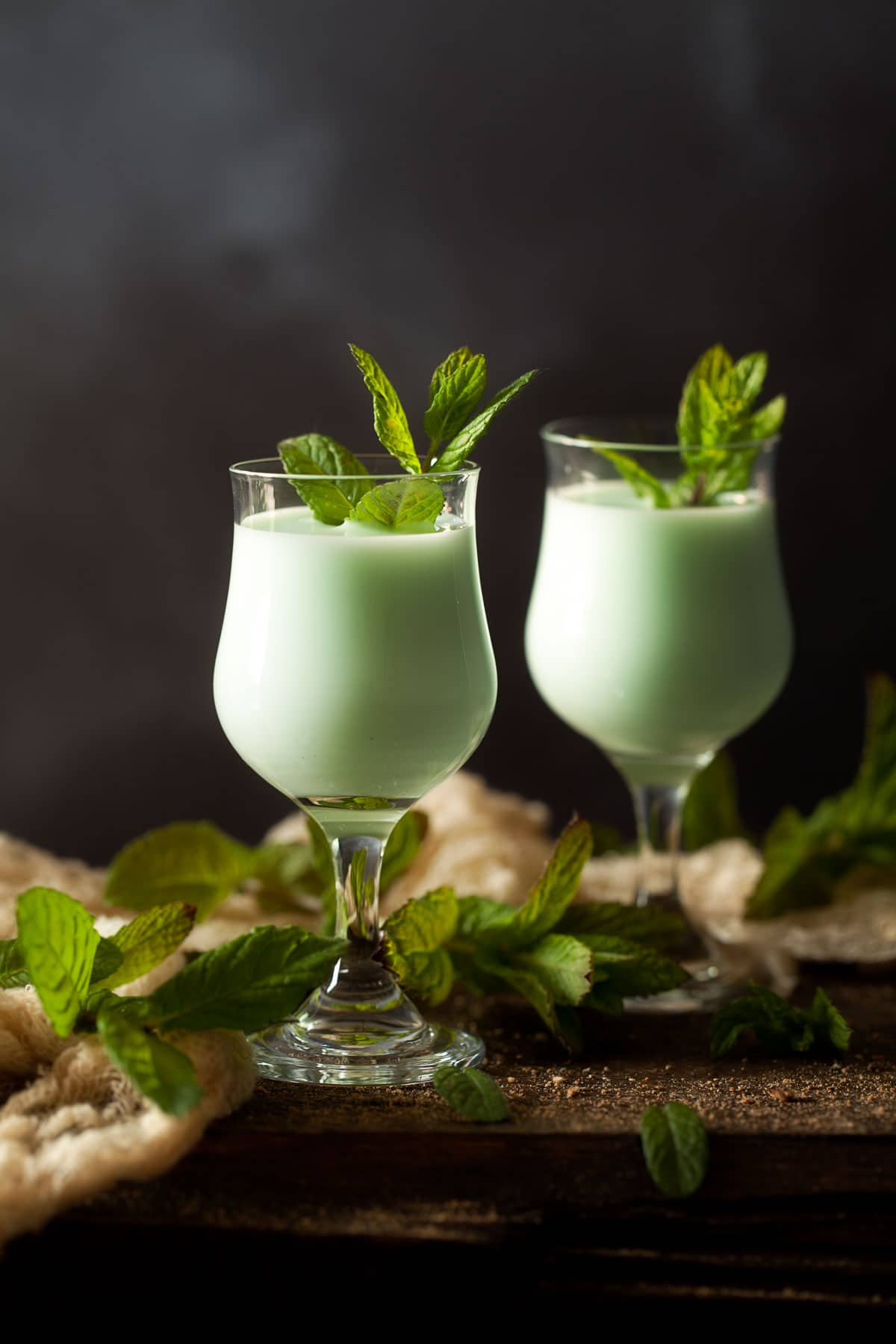Mint gin Alexander - a pale green creamy cocktail served in 2 vintage glasses and decorated with mint leaves