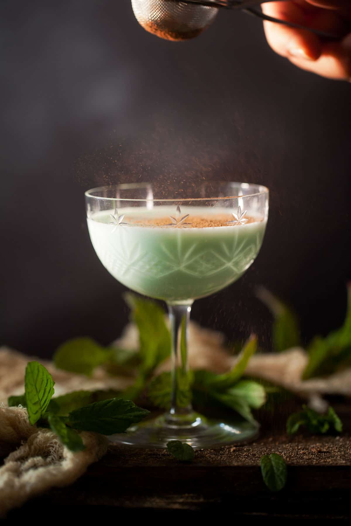 A creamy gin alexander cocktail flavoured with green creme de menthe. Served in a vintage cocktail glass with cocoa powder being dusted over the top