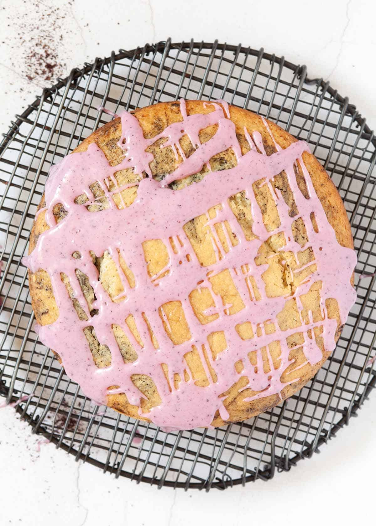 A round sponge cake topped with pink/ purple water icing in a criss-cross design