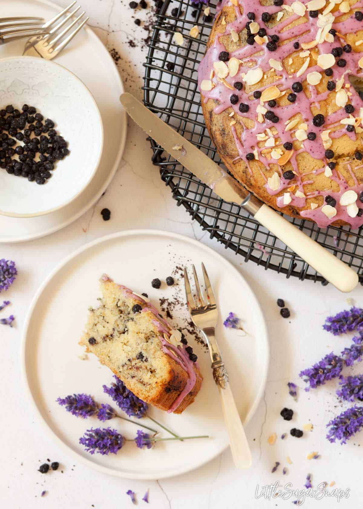 A slice of eggless blueberry cake on a plate with fresh lavender