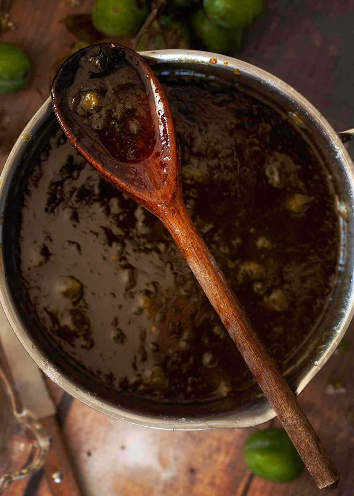 Process shot - cooked greengage jam in a saucepan with a wooden spoon resting on top