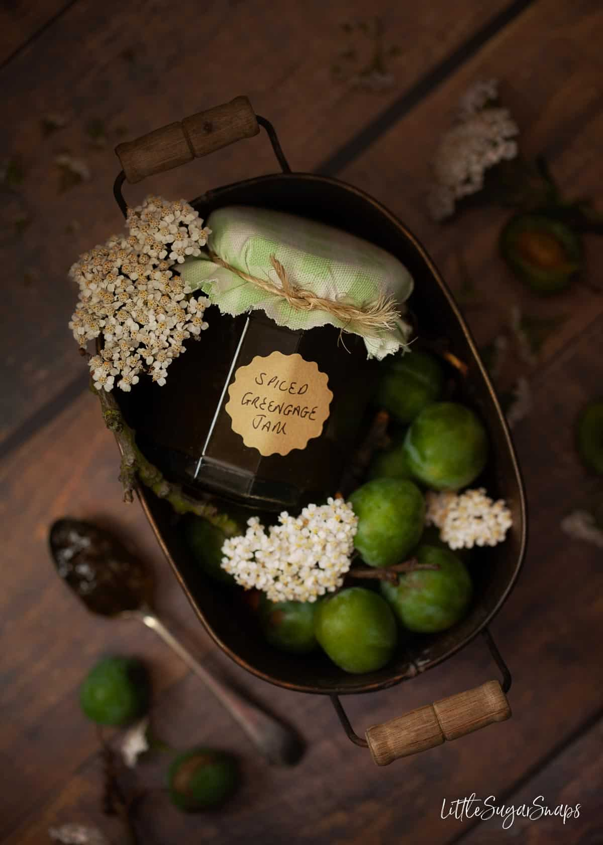 A tin caddy holding a jar of greengage jam and fresh greengages