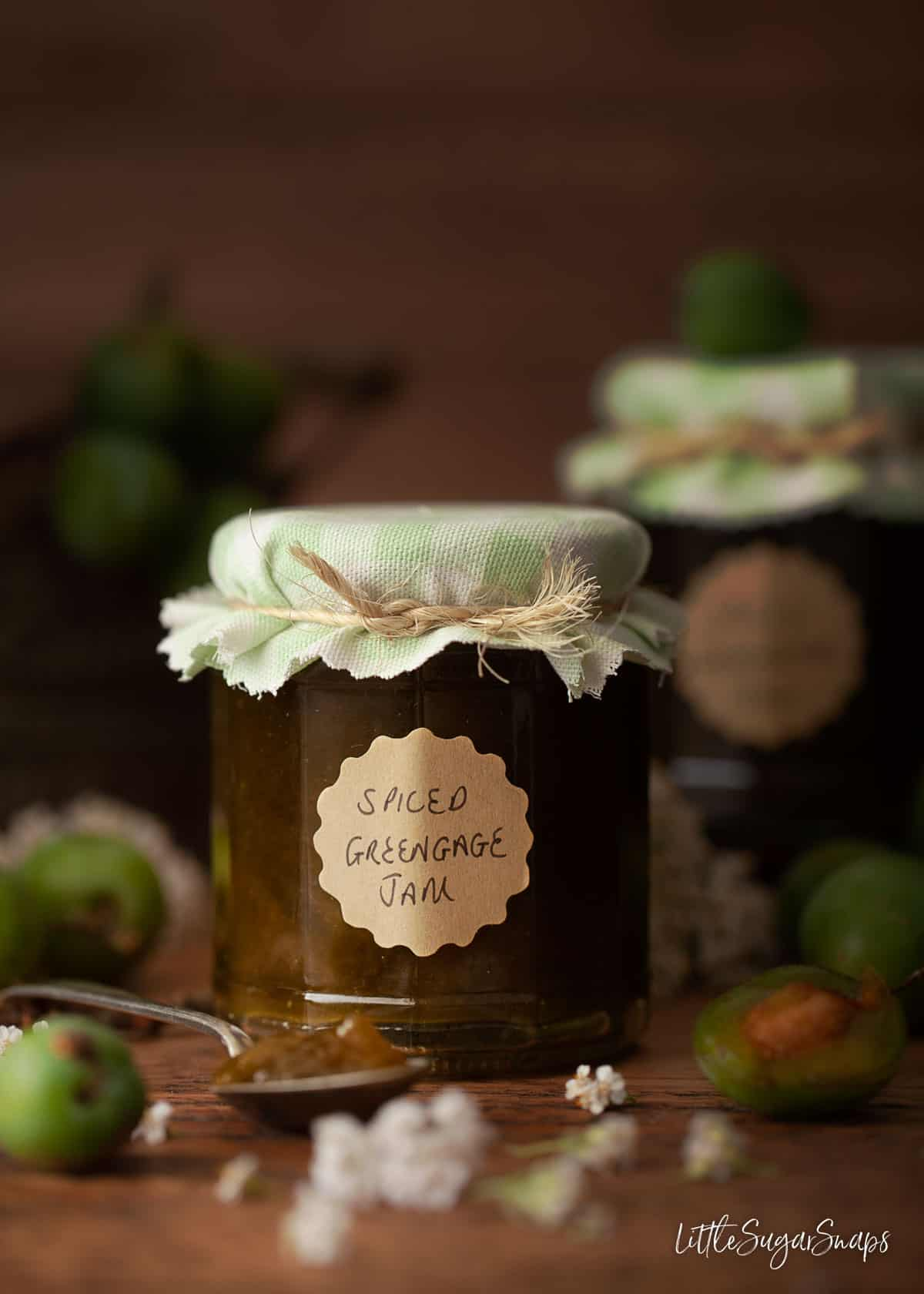 A jar of homemade greengage jam with fresh greengages on the tabletop.